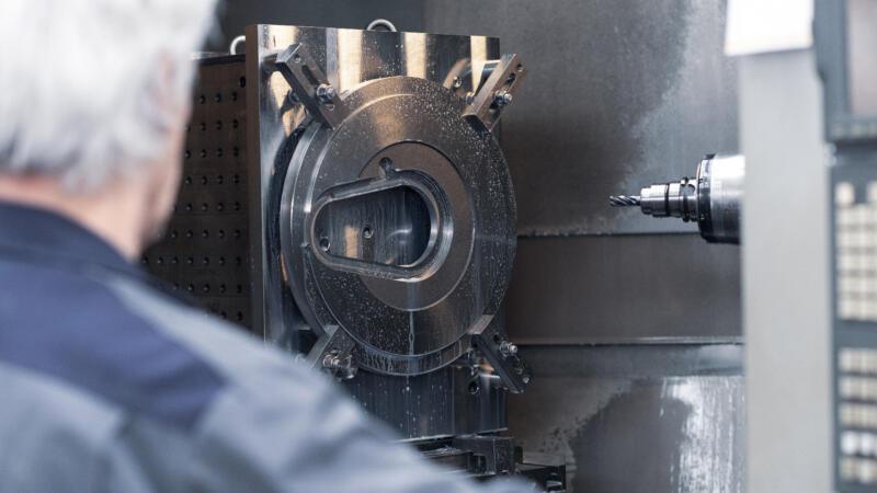 Mitarbeiter GROB AG an Fräsmaschine