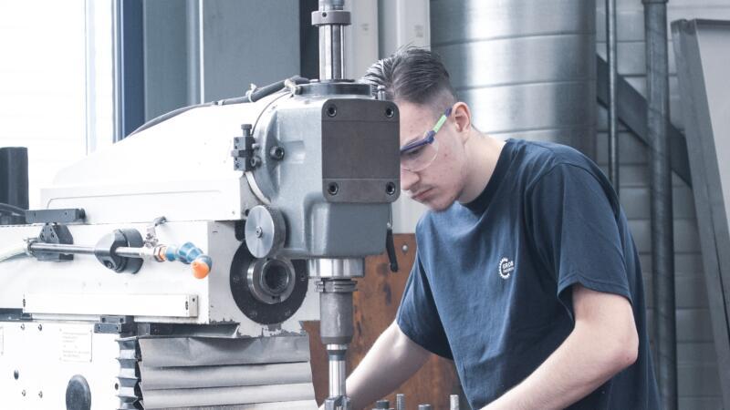 Auszubildender Polymechaniker an Maschine bei GROB AG